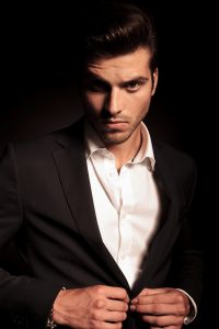portrait of a young fashion man buttoning his suit on black stud